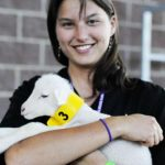 A third-year veterinary student cares for a lamb at the birthing center during the Iowa State Fair.]