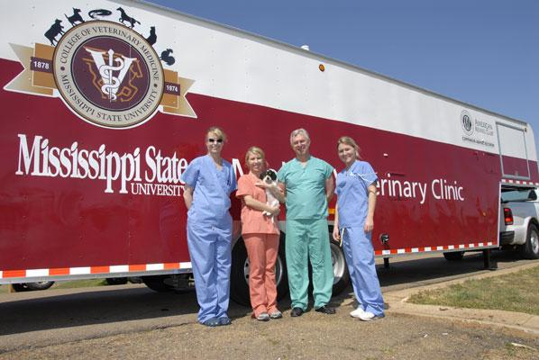 Dr. Bushby with three students next to the Mobile Veterinary Unit.