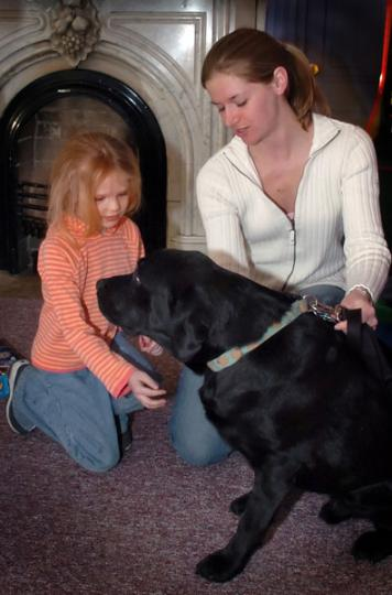 Purdue veterinary medicine student Jennifer Slack, right, and her dog, Riot, visit with a girl at a YWCA. Slack was enrolled in a course through which veterinary students teach children about proper animal care and bite prevention.