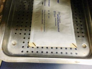 This single pouch is placed the correct way on an autoclave tray.
